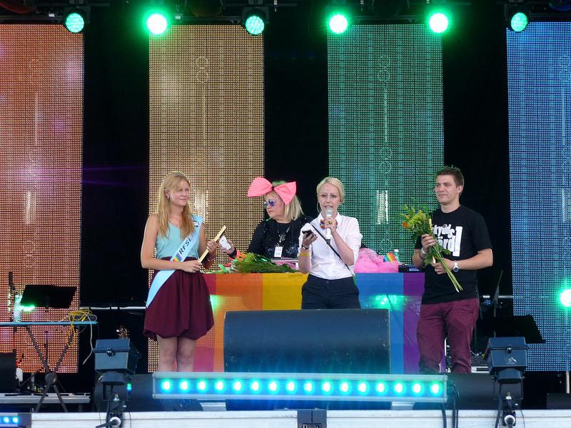 Kerstin Burman tar emot Regnbågspriset av RFSL Stockholms ordförande Kristin Arthur och vice ordförande Julle Bergenholtz.
