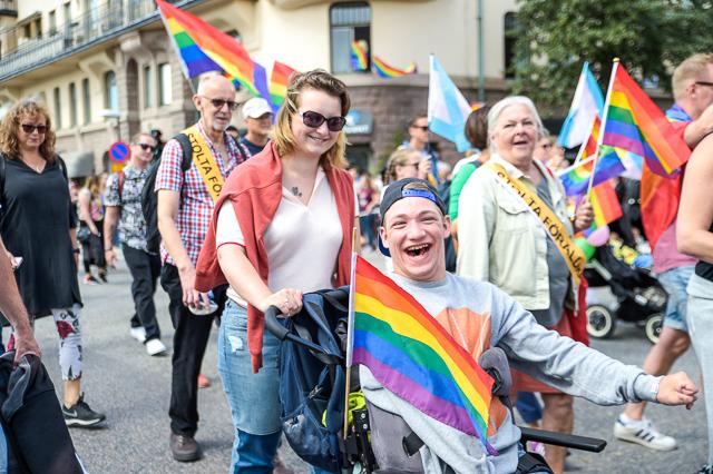 Människor med regnbågsflaggor i paraden. En leende person i rullstol.