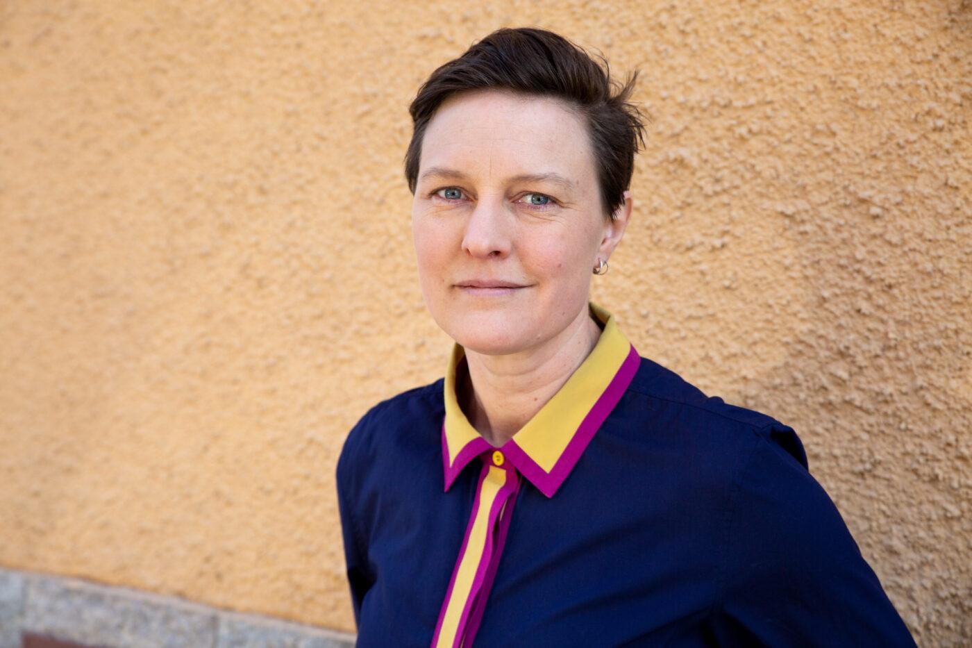 RFSL Stockholms ordförande Lovise Brade framför en gul fasad och tittar in i kameran